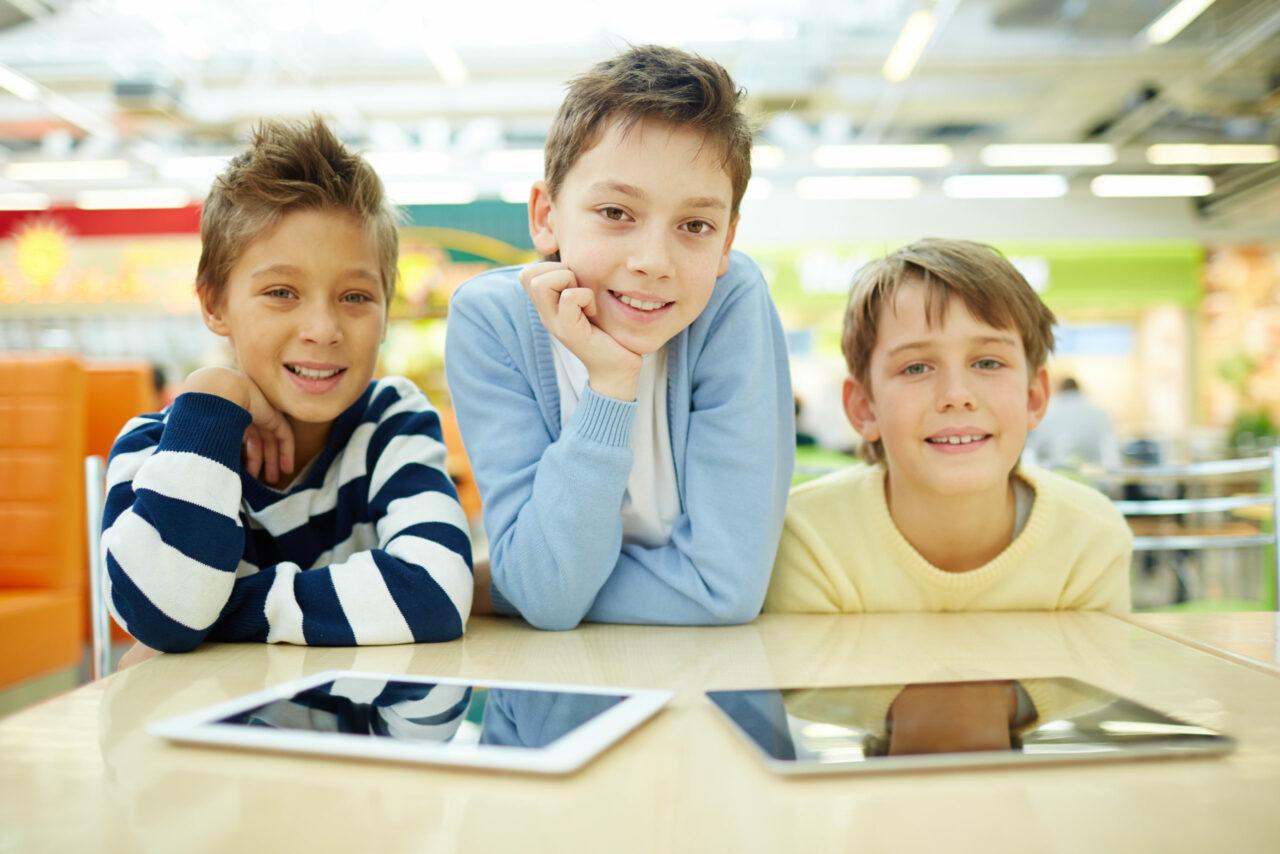 Tre drenge med iPads foran sig