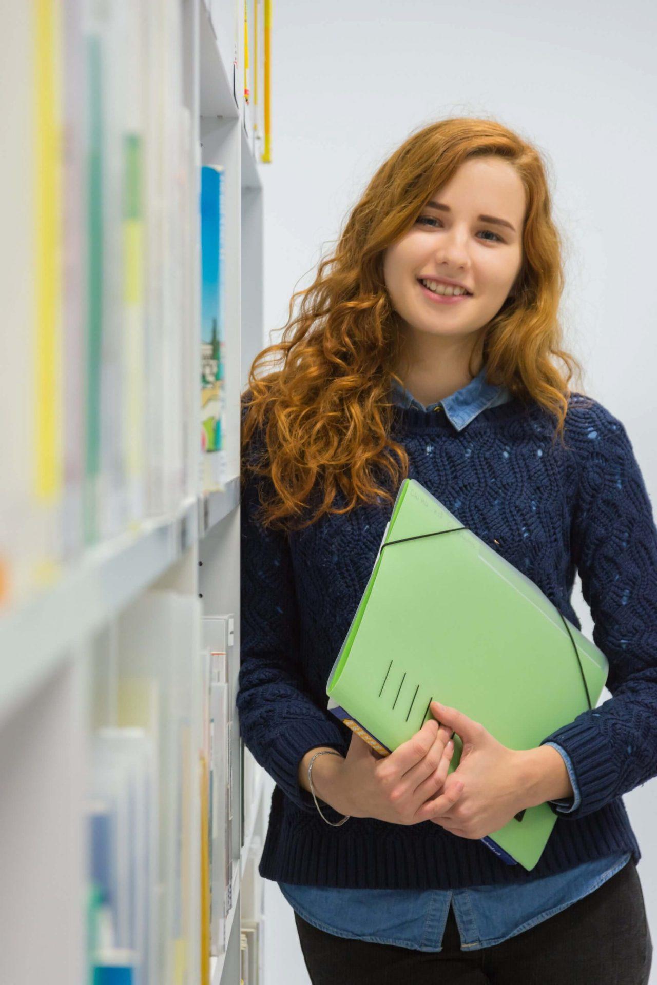 Ung kvindelig studerende står ved bogreol med mappe i hånden