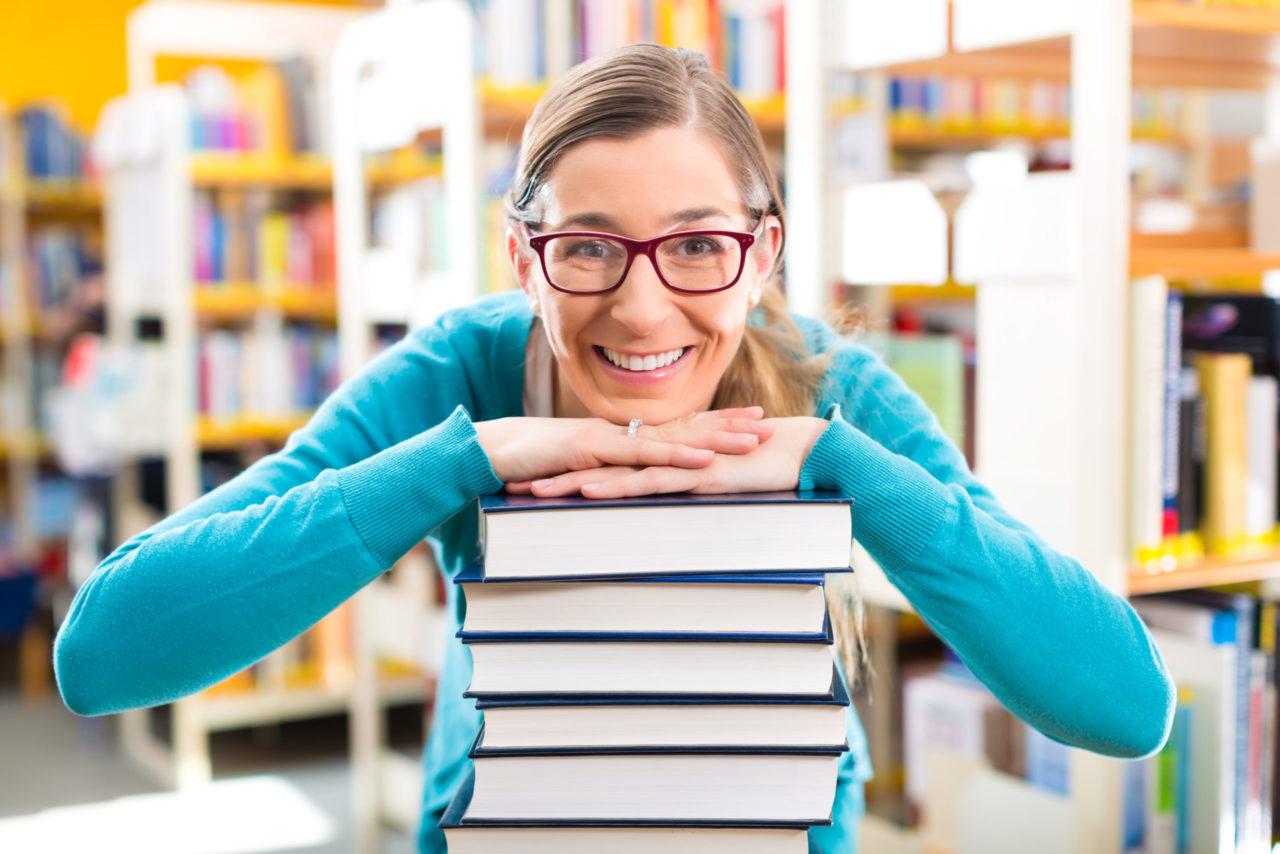 Ung kvinde smiler og har hagen på en stak bøger foran sig
