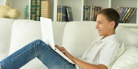 Ung mand sidder i sofaen hjemme med sin computer