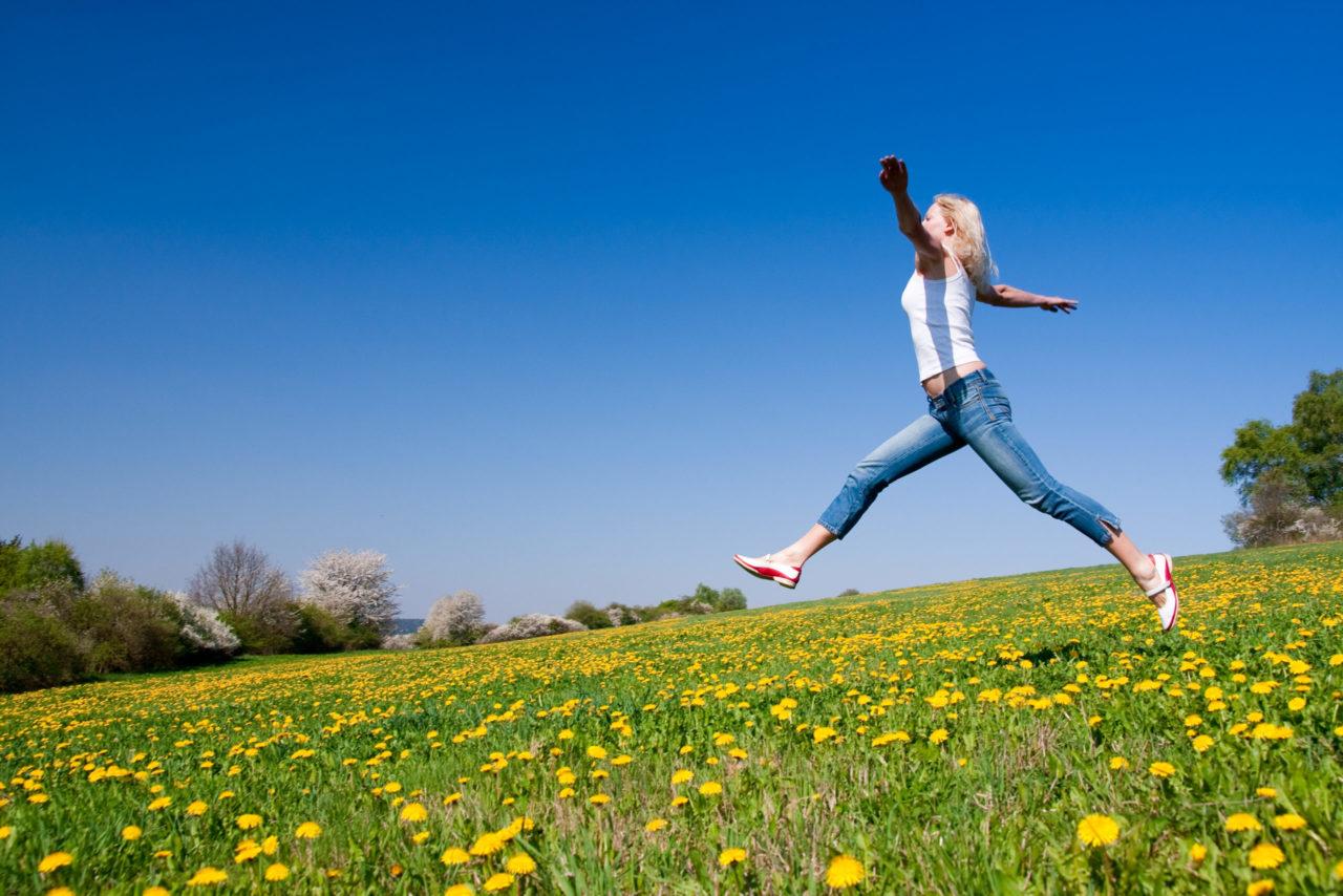 Kvinde springer afsted på grøn eng og himlen er blå