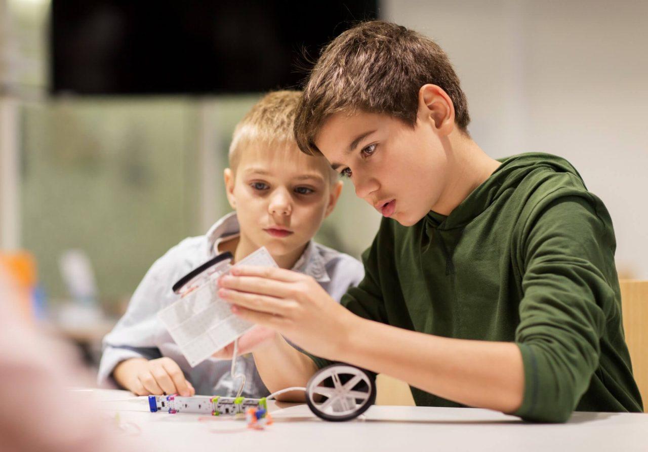 Drenge arbejder med at samle robot