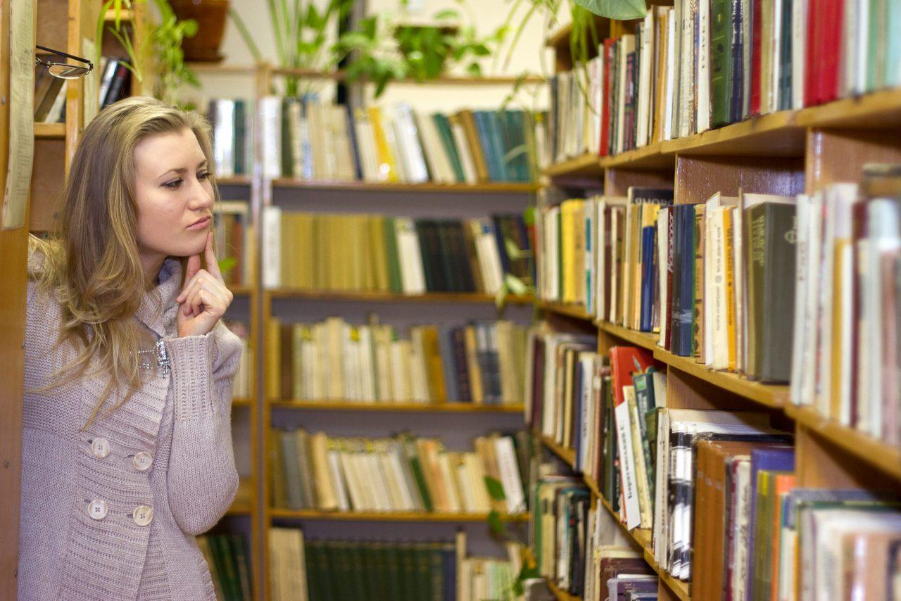 Ung pige der leder efter en bog på hylder med bøger